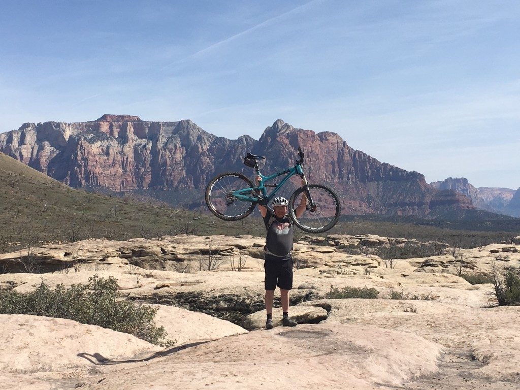 Riding the Guac loop with the cliffs of Zion National Park in the background.
